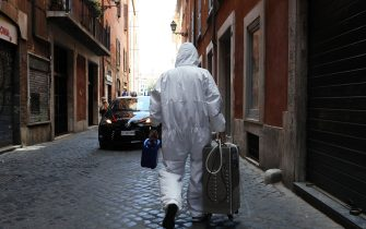 ROME, ITALY - MAY 15: A technician who has just sanitized a shop in central Rome walks down an alley at the end of his job on May 15, 2020 in Rome, Italy.  Italy was the first country to impose a nationwide lockdown to stem the transmission of the Coronavirus (Covid-19) and it has started to ease these restrictions in recent weeks. The initial reopening date decided by the government would have been June 1, but due to pressure from the regional governments, trade associations and the public, this process has been accelerated. However, many businesses have complained that the government has not provided complete safety guidelines for the various types of businesses permitted to reopen and, consequently, some have decided to postpone their opening. (Photo by Marco Di Lauro/Getty Images)