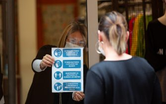 BOLOGNA, ITALY - MAY 18: A shop owner is putting a sing with rules to respect before entering into the shop like wearing mask, gloves and sanitize the hands. First day of reopening of the most part of activities on May 18, 2020 in Bologna, Italy. Restaurants, bars, cafes, hairdressers and other shops have reopened, subject to social distancing measures, after more than two months of a nationwide lockdown meant to curb the spread of Covid-19. (Photo by Max Cavallari/Getty Images)