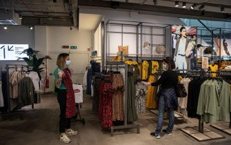 MILAN, ITALY - MAY 18: Two customers, wearing face masks, shop at the Corso Buenos Aires OVS fashion retail store on May 18, 2020 in Milan, Italy. Restaurants, bars, cafes, hairdressers and other shops have reopened, subject to social distancing measures, after more than two months of a nationwide lockdown meant to curb the spread of Covid-19. (Photo by Emanuele Cremaschi/Getty Images)