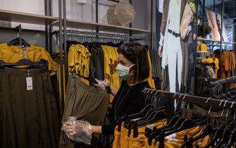 MILAN, ITALY - MAY 18: A customer, wearing a face mask, shops at the Corso Buenos Aires OVS fashion retail store on May 18, 2020 in Milan, Italy. Restaurants, bars, cafes, hairdressers and other shops have reopened, subject to social distancing measures, after more than two months of a nationwide lockdown meant to curb the spread of Covid-19. (Photo by Emanuele Cremaschi/Getty Images)