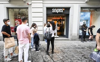 TURIN, ITALY - MAY 23: A group of people line-up waiting to enter the clothing store after its re-opening following more than two months of lockdown on May 23, 2020 in Turin, Italy. Restaurants, bars, cafes, hairdressers and other shops have reopened, subject to social distancing measures, after more than two months of a nationwide lockdown meant to curb the spread of Covid-19. (Photo by Diego Puletto/Getty Images)