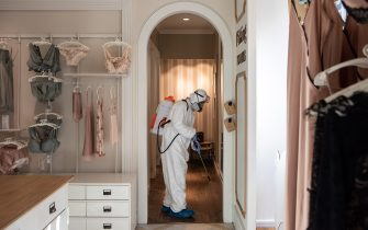MILAN, ITALY - APRIL 29: A utility service worker, wearing a protective suit, sprays sodium hypochlorite to disinfect the fitting rooms of a women underwear store  on April 29, 2020 in Milan, Italy. Italy will remain on lockdown to stem the transmission of the Coronavirus (Covid-19), slowly easing restrictions. (Photo by Emanuele Cremaschi/Getty Images)