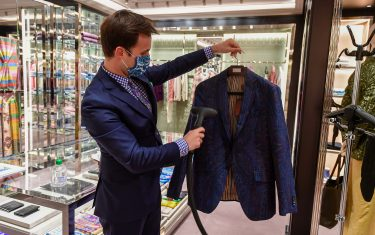 A seller steam sanitizes a jacket for a customer to try on at an Etro fashion shop on May 18, 2020 in Milan during the country's lockdown aimed at curbing the spread of the COVID-19 infection, caused by the novel coronavirus. - Restaurants and churches reopen in Italy on May 18, 2020 as part of a fresh wave of lockdown easing in Europe and the country's latest step in a cautious, gradual return to normality, allowing businesses and churches to reopen after a two-month lockdown. (Photo by Miguel MEDINA / AFP) (Photo by MIGUEL MEDINA/AFP via Getty Images)