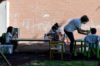 Foto Fabio Ferrari/LaPresse  26 Maggio 2020 Ivrea, Italia  News Emergenza COVID-19 (Coronavirus) - Fase 2 - Ivrea riapre le scuole: via libera all\'attività all\'aperto. Scuola all'aperto a Ivrea per aiutare le famiglie nel post lockdown. L'idea dell'amministrazione comunale che sperimenta il servizio per i bambini residenti in città tra i 3 e i 6 anni. Il progetto si svolge nei giardini delle scuole, Don Milani e Sant\'Antonio. È prevista un'area triage dove effettuare il controllo della temperatura per consentire l'accesso in sicurezza dei bimbi, seguiti dalle insegnanti degli asili nido comunali a gruppi di cinque.  Photo Fabio Ferrari/LaPresse  May 26, 2020 Ivrea, Italy  News COVID-19 emergency (Coronavirus) - Phase 2 - Ivrea reopens schools: green light for outdoor activities. Outdoor school in Ivrea to help families in the post lockdown. The idea of the municipal administration that tests the service for children living in the city between 3 and 6 years old. The project takes place in the school gardens, Don Milani and Sant\'Antonio. A triage area is provided for temperature control to allow safe access for children, followed by the teachers of the municipal nursery schools in groups of five.