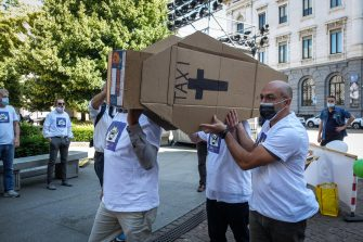 A group of taxi drivers belonging to the Assotaxi union protest to ask the municipal administration to gather the monitoring commission and listen to their proposals in Piazza Scala in front of the Municipality of Milan Palazzo Marino in Milan, Italy, 27 May 2020.A funeral procession, with a cardboard coffin with the words taxi, to stage the funeral of the category and ask for help to try to recover at least some customers in phase 2 thanks to the use of vouchers.  Ansa / Matteo Corner
