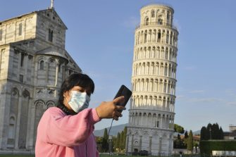PISA, ITALY - MAY 30:  Tourists wearing face masks pose for a photograph near the tower of Pisa on May 30, 2020 in Pisa, Italy. The city of Pisa in Piazza dei Miracoli celebrated the reopening of the Tower of Pisa and of the city to the world with a Flash Mob after the long lockdown due to the Coronavirus. There have been over 232,000 reported COVID-19 cases in Italy and more than 33,000 deaths.  (Photo by Laura Lezza/Getty Images)