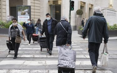 TURIN, ITALY - MAY 29: People wearing a protective mask walk crosswalk in the streets of the city center on May 29, 2020 in Turin, Italy. The Piedmont Region in complete autonomy declared that from today 29 May it is mandatory to use the protective mask even outdoors to prevent further infections from Coronavirus (Covid 19). Many Italian businesses have been allowed to reopen, after more than two months of a nationwide lockdown meant to curb the spread of Covid-19. (Photo by Stefano Guidi/Getty Images)