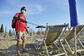 PISA, ITALY - MAY 24:  A lifeguard on the beach wearing a protective mask carries out sanitation and disinfection operations with disinfectant during the Coronavirus pandemic in a bathhouse near Pisa on May 25, 2020 in Pisa, Italy. From 18 May access to the sea is allowed, with strict rules region by region. The bathing establishments have reopened, subject to social distancing measures, after more than two months of a nationwide lockdown and following the anti-contagion rules for Coronavirus with umbrellas spaced about 3 meters apart. There have been over 229,000 reported COVID-19 cases in Italy and more than 32,000 deaths.  (Photo by Laura Lezza/Getty Images)