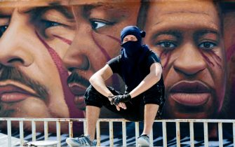 Italian street artist Jorit Agoch poses next to his latest work, a huge mural in memory of George Floyd, in Naples, southern Italy, 04 June 2020. Faces of Lenin, Martin Luther King, Malcom X and Angela Davis are also painted on the mural. ANSA/ CIRO FUSCO