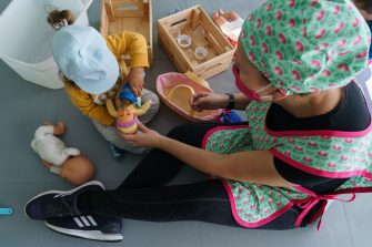 A teacher wearing a face mask attends a child at the Palotes preschool  in Valladolid, on June 10, 2020. - The Palotes preschool is one of the first schools to open in the Castilla y Leon region as the country continues to loosen a national lockdown to stop the spread of the novel coronavirus. (Photo by CESAR MANSO / AFP) (Photo by CESAR MANSO/AFP via Getty Images)
