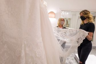 CATANIA, ITALY - MAY 06: Stylist Mariella Gennarino (L) assists a client who is soon to get married, while she chooses a wedding dress in the atelier in Catania open to the public again after the lockdown on May 6, 2020 in Catania, Italy. Italy will remain on lockdown to stem the transmission of the Coronavirus (Covid-19), slowly easing restrictions. (Photo by Fabrizio Villa/Getty Images)