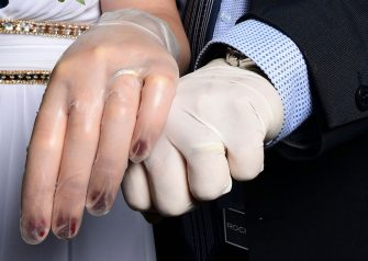 TOPSHOT - Newly-wed Italians Ester Concilio (L) and Rafaele Carbonelli show wedding rings under the protective gloves following the ceremony at the Briosco's town hall, about 45 km ( 28 miles) north of Milan, on May 11, 2020 during the country's lockdown aimed at curbing the spread of the COVID-19 infection, caused by the novel coronavirus. (Photo by Miguel MEDINA / AFP) (Photo by MIGUEL MEDINA/AFP via Getty Images)