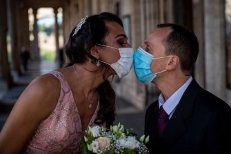 ROME, ITALY - APRIL 24: Sergio and Sophia kiss each other wearing protective masks after their wedding ceremony at Campidoglio, during the Coronavirus (COVID-19) pandemic, on April 24, 2020 in Rome, Italy. Italy is still remaining on lockdown until May 4th to stem the transmission of the Coronavirus (Covid-19). (Photo by Antonio Masiello/Getty Images)
