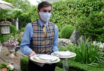 A waiter from The Inn at Little Washington, one of the countrys most renowned restaurants, wears a face mask on the first day of Virginia's phase one reopening in Washington, Virginia on May 29, 2020. - Today marks the beginning of phase one in the state with restaurants reopening following the stay at home orders from the COVID-19 pandemic, provided they can serve customers outdoors with groups sitting at least 6 feet apart. (Photo by Olivier DOULIERY / AFP) (Photo by OLIVIER DOULIERY/AFP via Getty Images)