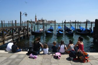 People sit by gondolas moored at Riva degli Schiavoni with San Giorgio Maggiore church in background, on June 12, 2020 in Venice as the country eases its lockdown aimed at curbing the spread of the COVID-19 infection, caused by the novel coronavirus. (Photo by ANDREA PATTARO / AFP) (Photo by ANDREA PATTARO/AFP via Getty Images)
