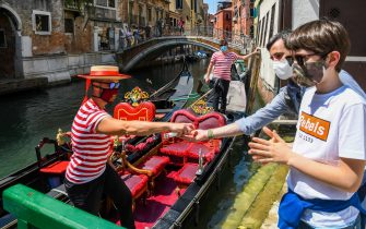A gondolier (L) sprays sanitizer on his customers' hands prior to going for a gondola ride on a canal in Venice on June 12, 2020 as the country eases its lockdown aimed at curbing the spread of the COVID-19 infection, caused by the novel coronavirus. (Photo by ANDREA PATTARO / AFP) (Photo by ANDREA PATTARO/AFP via Getty Images)