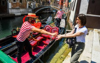 A gondolier (L) sprays sanitizer on a customer's hands prior to going for a gondola ride on a canal in Venice on June 12, 2020 as the country eases its lockdown aimed at curbing the spread of the COVID-19 infection, caused by the novel coronavirus. (Photo by ANDREA PATTARO / AFP) (Photo by ANDREA PATTARO/AFP via Getty Images)