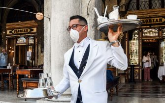 TOPSHOT - A waiter serves customers on June 12, 2020 at the terrace of the 18th Century Cafe Florian on St. Mark's Square in Venice, which reopens after being closed for three months during the country's lockdown aimed at curbing the spread of the COVID-19 infection, caused by the novel coronavirus. (Photo by ANDREA PATTARO / AFP) (Photo by ANDREA PATTARO/AFP via Getty Images)