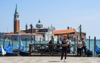 Gondoliers wait for customers at Riva degli Schiavoni with San Giorgio Maggiore church in background, on June 12, 2020 in Venice as the country eases its lockdown aimed at curbing the spread of the COVID-19 infection, caused by the novel coronavirus. (Photo by ANDREA PATTARO / AFP) (Photo by ANDREA PATTARO/AFP via Getty Images)