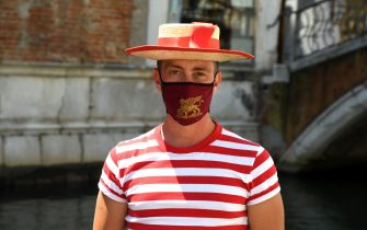 A gondolier, wearing a face mask showing the winged lion of Venice, looks on prior to going for a gondola ride with customers on a canal in Venice on June 12, 2020 as the country eases its lockdown aimed at curbing the spread of the COVID-19 infection, caused by the novel coronavirus. (Photo by ANDREA PATTARO / AFP) (Photo by ANDREA PATTARO/AFP via Getty Images)