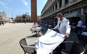 A waiter sets a table on June 12, 2020 at the terrace of the 18th Century Cafe Florian on St. Mark's Square in Venice, which reopens after being closed for three months during the country's lockdown aimed at curbing the spread of the COVID-19 infection, caused by the novel coronavirus. (Photo by ANDREA PATTARO / AFP) (Photo by ANDREA PATTARO/AFP via Getty Images)