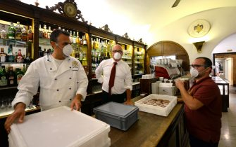 A view shows bartenders and employees at 18th Century Cafe Florian on June 12, 2020 on St. Mark's Square in Venice, which reopens after being closed for three months during the country's lockdown aimed at curbing the spread of the COVID-19 infection, caused by the novel coronavirus. (Photo by ANDREA PATTARO / AFP) (Photo by ANDREA PATTARO/AFP via Getty Images)