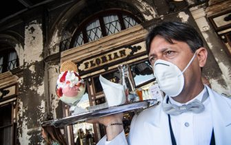 VENICE, ITALY - JUNE 12: Workers of the Florian Cafè serve customers at the reopening after 3 months of closure due to Covid-19 on June 12, 2020 in Venice, Italy. The whole country is returning to normality after more than two months of a nationwide lockdown meant to curb the spread of Covid-19. (Photo by Simone Padovani/Awakening/Getty Images)