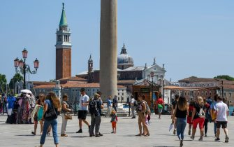 People walk across Piazza Riva degli Schiavoni with San Giorgio Maggiore church in background, on June 12, 2020 in Venice as the country eases its lockdown aimed at curbing the spread of the COVID-19 infection, caused by the novel coronavirus. (Photo by ANDREA PATTARO / AFP) (Photo by ANDREA PATTARO/AFP via Getty Images)