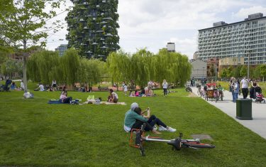 "MILAN, ITALY - JUNE 13: People sit in the grass and walk on the paths at the ""Biblioteca degli Alberi"" park, Porta Nuova Park on June 13, 2020 in Milan, Italy. The whole country is returning to normality after more than two months of a nationwide lockdown meant to curb the spread of Covid-19. (Photo by Fabrizio Villa/Getty Images)"
