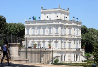 This picture taken on June 11, 2009 shows flags floating atop the 17th-century palace Villa Doria Pamphili in Rome which host the Libyan leader Moamer Kadhafi during his first visit to Italy. The Libyan leader has also pitched his trademark tent in the park . AFP PHOTO / TIZIANA FABI (Photo credit should read TIZIANA FABI/AFP via Getty Images)