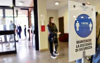 Una studentessa entra a scuola indossando una mascherina chirurgica anticoronavirus