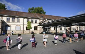 Children queue to enter their classrooms at the Ziegelau elementary school in Strasbourg, eastern France, as primary and middle schools reopen in France on June 22, 2020. - After six weeks of unsteady school sessions and more than three months of class at home to fight against the spread of the new coronavirus Covid-19, French pupils and middle school students return to class on June 22, thanks to a lighter health protocol. (Photo by FREDERICK FLORIN / AFP) (Photo by FREDERICK FLORIN/AFP via Getty Images)