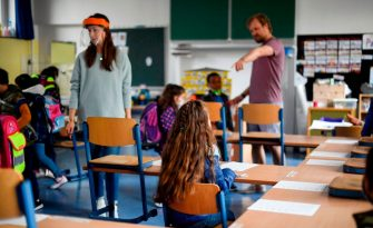 Teachers give instructions to their students in a classroom of the Petri primary school in Dortmund, western Germany, on June 15, 2020 amid the novel coronavirus COVID-19 pandemic. - From June 15, 2020, all children of primary school age in the western federal state of North Rhine-Westphalia will once again be attending regular daily classes until the summer holidays. The distance rules and compulsory mouthguards are no longer applicable. (Photo by Ina FASSBENDER / AFP) (Photo by INA FASSBENDER/AFP via Getty Images)