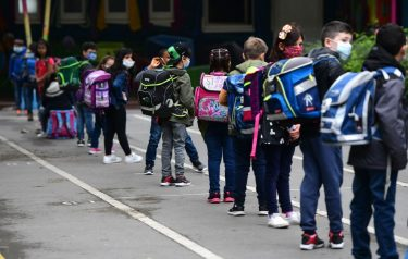 Students line up for the entrance at the schoolyard of the Petri primary school in Dortmund, western Germany, on June 15, 2020 amid the novel coronavirus COVID-19 pandemic. - From June 15, 2020, all children of primary school age in the western federal state of North Rhine-Westphalia will once again be attending regular daily classes until the summer holidays. The distance rules and compulsory mouthguards are no longer applicable. (Photo by Ina FASSBENDER / AFP) (Photo by INA FASSBENDER/AFP via Getty Images)