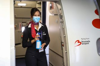 A cabin crew member wearing a protective face mask, holds hydroalcoholic gel at the entrance of a Brussels Airlines plane, at Brussels Airport, in Zaventem, on June 15, 2020 as Brussels Airport reopens for travels within Europe and the Schengen zone, after a months-long closure aimed at stemming the spread of the COVID-19 pandemic, caused by the novel coronavirus. (Photo by BRUNO FAHY / Belga / AFP) / Belgium OUT (Photo by BRUNO FAHY/Belga/AFP via Getty Images)