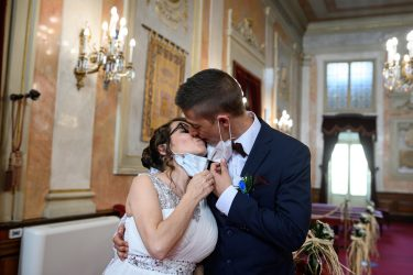 epa08469982 Groom Iker (R) and bride Aranzazu (L) lower their face masks to kiss during their civil wedding at the town hall of Alcala de Henares, Madrid, Spain, 06 June 2020. The nuptial ceremony was one of the first held there since the the state of emergency was implemented in March throughout Spain due to the pandemic COVID-19 disease caused by the SARS-CoV-2 coronavirus. The current regulations for marriages stipulate a maximum number of 10 guests and the mandatory use of protective face masks.  EPA/FERNANDO VILLAR