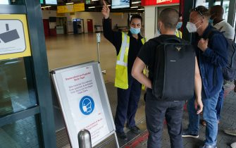 BERLIN, GERMANY - JUNE 19: An airport worker wearing a protective face mask, who said she did not mind being photographed, directs tarvellers at Tegel Airport during the novel coronavirus pandemic on June 19, 2020 in Berlin, Germany. While travel restrictions put in place across the European Union in March to stem the spread of the virus have recently been mostly lifted ahead of the economically crucial summer tourist season, travel is picking up only slowly and the number of flights on offer remains low for many destinations.  (Photo by Sean Gallup/Getty Images)