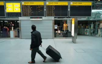 BERLIN, GERMANY - JUNE 19: A man pulling a suitcase walks past a flight arrivals board that shows only a fraction of flights compared to before the pandemic at Tegel Airport during the novel coronavirus pandemic on June 19, 2020 in Berlin, Germany. While travel restrictions put in place across the European Union in March to stem the spread of the virus have recently been mostly lifted ahead of the economically crucial summer tourist season, travel is picking up only slowly and the number of flights on offer remains low for many destinations.  (Photo by Sean Gallup/Getty Images)