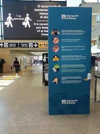 Maxi totem informativi con raccomandazioni ai passeggeri e dispenser di gel igienizzante per prevenire il contagio da coronavirus all'aeroporto di Fiumicino (Roma), 18 marzo 2020.  ANSA / TELENEWS