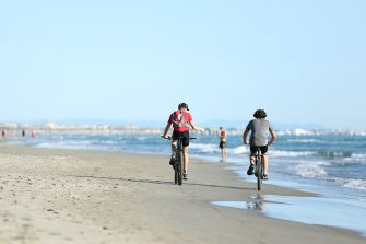 FORTE DEI MARMI, ITALY - MAY 04: People ride bikes on the beach on May 04, 2020 in Forte dei Marmi, Italy. Italy was the first country to impose a nationwide lockdown to stem the transmission of the Coronavirus (Covid-19), and its restaurants, theaters and many other businesses remain closed. (Photo by Maria Moratti/Getty Images)