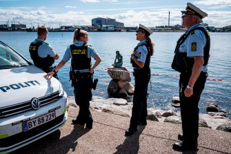"""Policemen stand on July 3, 2020 in front of the """"Little Mermaid"""" sculpture after it has been vandalised in Copenhagen. (Photo by Niels Christian Vilmann / Ritzau Scanpix / AFP) / Denmark OUT (Photo by NIELS CHRISTIAN VILMANN/Ritzau Scanpix/AFP via Getty Images)"""