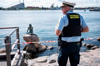 """A policeman stands on July 3, 2020 in front of the """"Little Mermaid"""" sculpture after it has been vandalised in Copenhagen. (Photo by Niels Christian Vilmann / Ritzau Scanpix / AFP) / Denmark OUT (Photo by NIELS CHRISTIAN VILMANN/Ritzau Scanpix/AFP via Getty Images)"""
