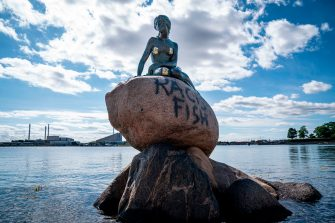 """A picture taken on July 3, 2020 shows a view of the """"Little Mermaid"""" sculpture after it has been vandalised with stickers and racist graffitis in Copenhagen. (Photo by Niels Christian Vilmann / Ritzau Scanpix / AFP) / Denmark OUT (Photo by NIELS CHRISTIAN VILMANN/Ritzau Scanpix/AFP via Getty Images)"""