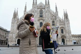 Two tourists from Argentina wearing respiratory masks walk while holding a tourist map in Piazza Duomo in Milan, on March 5. 2020. - Italy closed all schools and universities until March 15 to help combat the spread of the novel coronavirus crisis. The government decision was announced moments after health officials said the death toll from COVID-19 had jumped to 107 and the number of cases had passed 3,000. (Photo by Piero CRUCIATTI / AFP) (Photo by PIERO CRUCIATTI/AFP via Getty Images)