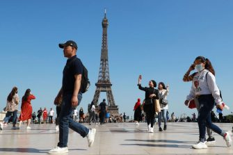 People, some wearing a face mask, walk on the Trocadero Plaza in front of the Eiffel Tower, on June 22, 2020, in Paris. (Photo by Ludovic MARIN / AFP) (Photo by LUDOVIC MARIN/AFP via Getty Images)