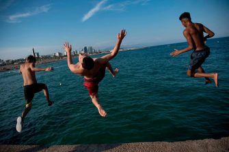Men dive at El Bogatell Beach in Barcelona on July 1, 2020. - The European Union reopened its borders to visitors from 15 countries but excluded the United States, where coronavirus deaths are spiking once again, six months after the first cluster was reported in China. (Photo by Josep LAGO / AFP) (Photo by JOSEP LAGO/AFP via Getty Images)