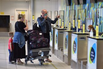 SOUTHEND-ON-SEA, ENGLAND  - JULY 01: A family hold up information as they check in their bags at the bag drop for Ryanair flight FR2190 to Malaga at London Southend Airport on July 1, 2020 in Southend-on-Sea, England. The airport opened its doors today for the first passenger holiday flight since the coronavirus pandemic lockdown to Malaga with Ryanair. The flight FR2190 left with 144 passengers on board. (Photo by John Keeble/Getty Images)