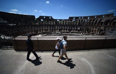 Visitors (C) followed by a member of security staff, walk across the Colosseum monument which reopens to the public on June 1, 2020 in Rome, while the country eases its lockdown aimed at curbing the spread of the COVID-19 infection, caused by the novel coronavirus. - The Colosseum monument reopens on June 1, 2020 after having been closed since March 8, 2020, with adequate sanitary protection for staff and visitors, secure routes, compulsory reservations and modified schedules to avoid crowds at peak times. (Photo by Filippo MONTEFORTE / AFP) (Photo by FILIPPO MONTEFORTE/AFP via Getty Images)