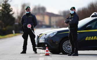 Green Berets from the Italian Finance guard (Guardia di Finanza) officers patrol by a check-point at one of the entrance of the small town of San Fiorano southeast of Milan, on February 26, 2020, situated in the red zone of the COVID-19 the novel coronavirus outbreak in northern Italy. (Photo by Miguel MEDINA / AFP) (Photo by MIGUEL MEDINA/AFP via Getty Images)