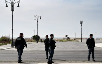 Italian Police officers wearing facemasks for protective measures, control the access to the pier in Ostia, in the outskirts of Rome, on March 21, 2020 following an order by the mayor of Rome asking to close the beaches of the capital during the country's lockdown aimed at stopping the spread of the COVID-19, the novel coronavirus. - Italy reported a record 627 new coronavirus deaths on March 20, 2020 and saw its world-topping toll surpass 4,000, despite government efforts to stem the pandemic's spread. (Photo by Alberto PIZZOLI / AFP) (Photo by ALBERTO PIZZOLI/AFP via Getty Images)